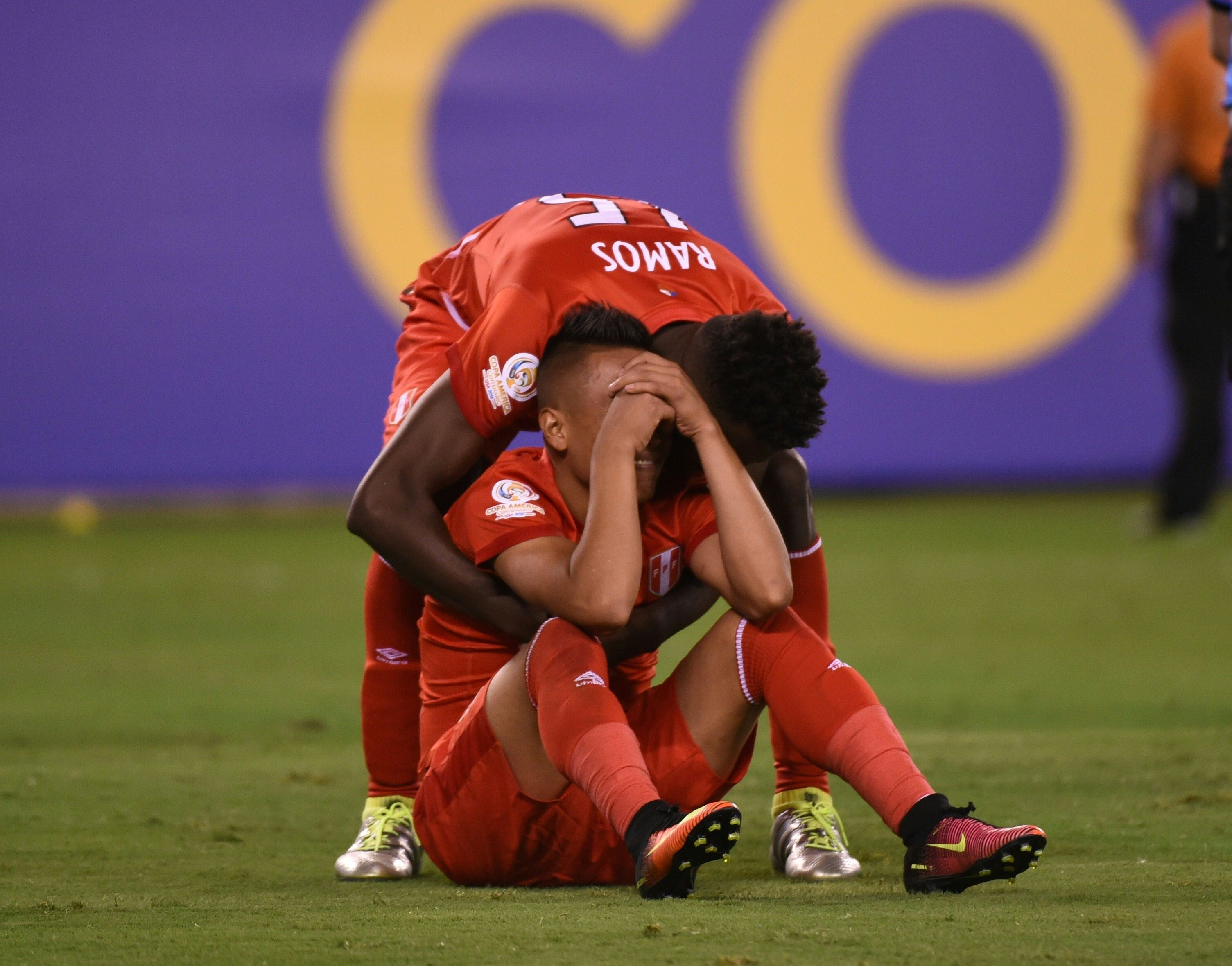 Peru's Christian Cueva (sitting on ground) is comforted by teammate C